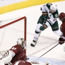 Minnesota Wild's Zach Parise (11) scores a game-tying goal against Arizona Coyotes' Devan Dubnyk (40) during the third period of an NHL hockey game Saturday, Dec. 13, 2014, in Glendale, Ariz. The Wild defeated the Coyotes 4-3 in a shootout The Associated