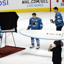 San Jose Sharks' Scott Hannan (27) is presented with a surfboard from teammates to commemorate Hannan's 1,000th game before an NHL hockey game against the New York Islanders Saturday, Nov. 1, 2014, in San Jose, Calif The Associated Press
