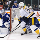 Toronto Maple Leafs goaltender Jonathan Bernier, left, makes a save as Nashville Predators' Viktor Stalberg comes around the net during the first period of an NHL hockey game, Thursday, Nov. 21, 2013 in Toronto The Associated Press