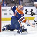Los Angeles Kings Jeff Carter (77) watches the puck go in the net past Edmonton Oilers goalie Ben Scrivens (30) during first period NHL hockey action in Edmonton, Canada, Sunday March 9, 2014. (AP Photo/The Canadian Press, Jason Franson)