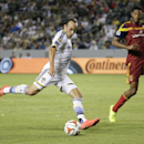 In this Saturday, July 12, 2014, photo, Los Angeles Galaxy's Landon Donovan, center, shoots as he is defended by Real Salt Lake's Chris Schuler during the second half of their MLS soccer match in Carson, Calif. Donovan says he will retire from professiona