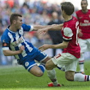 Arsenal's Nacho Monreal, fights for the ball with Wigan Athletic's Callum McManaman, during their English FA Cup semifinal soccer match, at the Wembley Stadium in London, Saturday, April 12, 2014