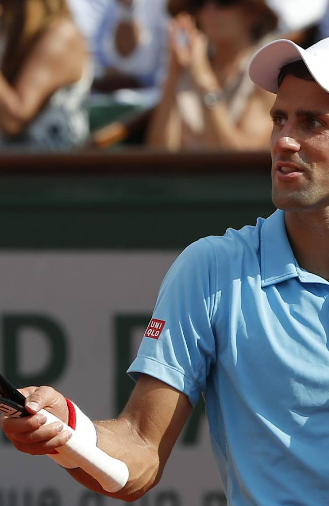 Serbia's Novak Djokovic gestures after missing a return during the final of the French Open tennis tournament against Spain's Rafael Nadal at the Roland Garros stadium, in Paris, France, Sunday, June 8, 2014