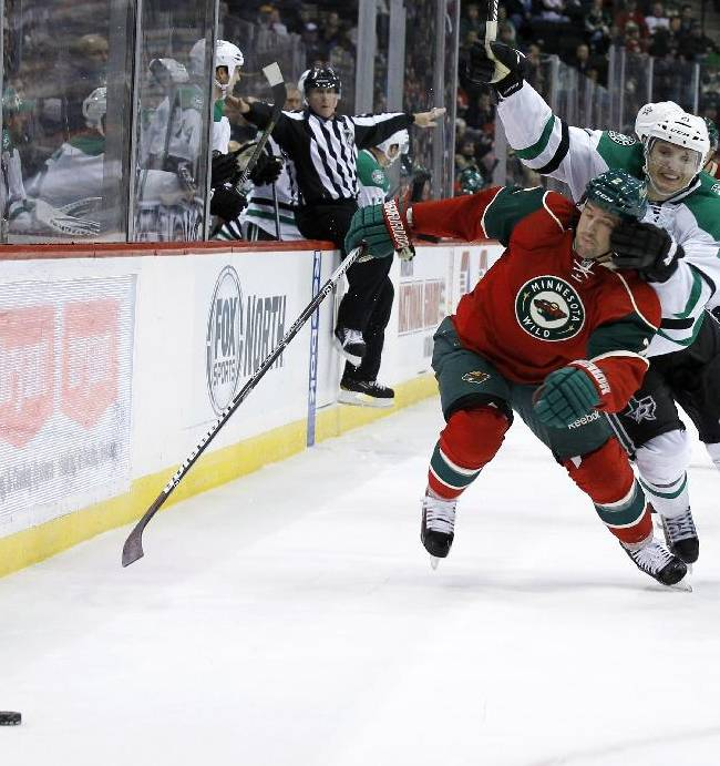 Minnesota Wild defenseman Keith Ballard, right front, gets tangled with Dallas Stars left wing Antoine Roussel (21) during the second period of an NHL hockey game in St. Paul, Minn., Saturday, Oct. 12, 2013