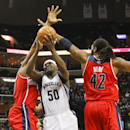 Memphis Grizzlies forward Zach Randolph (50) drives to the basket between Washington Wizards center Kevin Seraphin, left, and forward Nene (42) in the second half of an NBA basketball game, Tuesday, Feb. 11, 2014, in Memphis, Tenn. The Grizzlies won 92-89