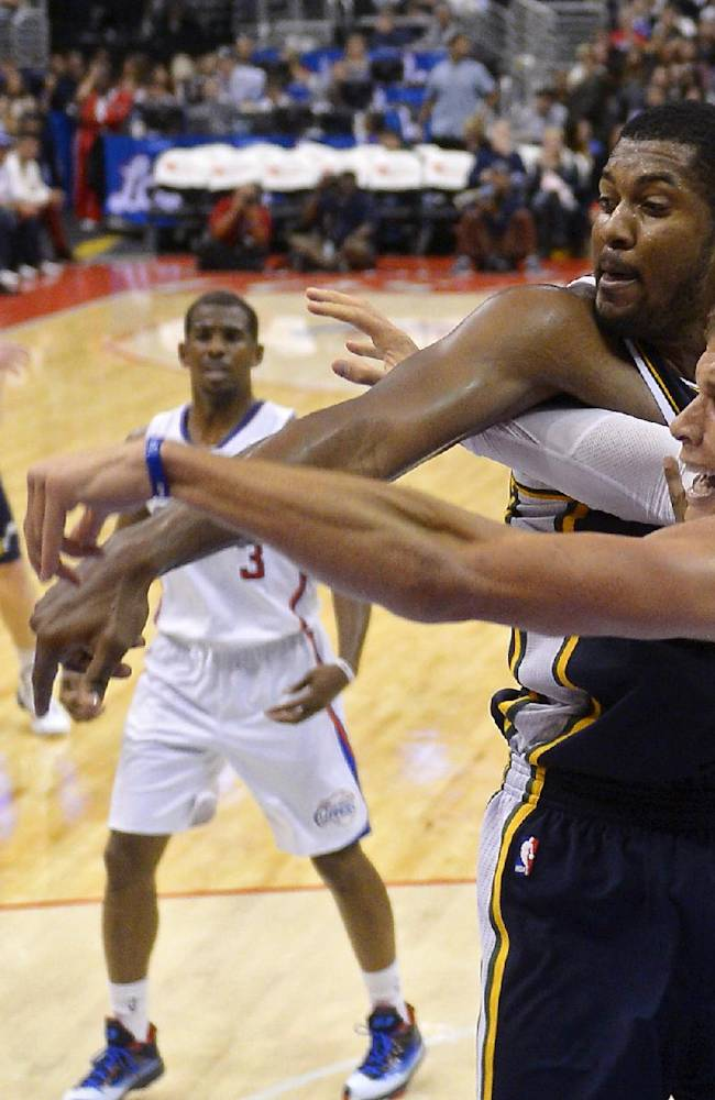 Utah Jazz power forward Derrick Favors, left, and Los Angeles Clippers power forward Blake Griffin go after a rebound during the second half of their NBA basketball game, Wednesday, Oct. 23, 2013, in Los Angeles