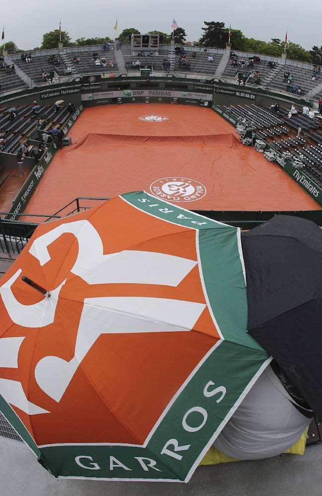 Tennis fans wait for the start of the first round match between Japan's Kei Nishikori and Slovakia's Martin Klizan at the French Open tennis tournament at the Roland Garros stadium, in Paris, France, Monday, May 26, 2014. Rain caused delay in the match schedule Monday