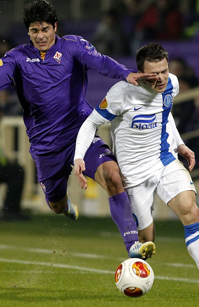 Fiorentina's Facundo Roncaglia, left, challenges for the ball with Dnipro Dnipropetrovsk's Yevhen Konoplyanka during their Europa League Group E soccer match at the Artemio Franchi stadium in Florence, Italy, Thursday, Dec. 12, 2013