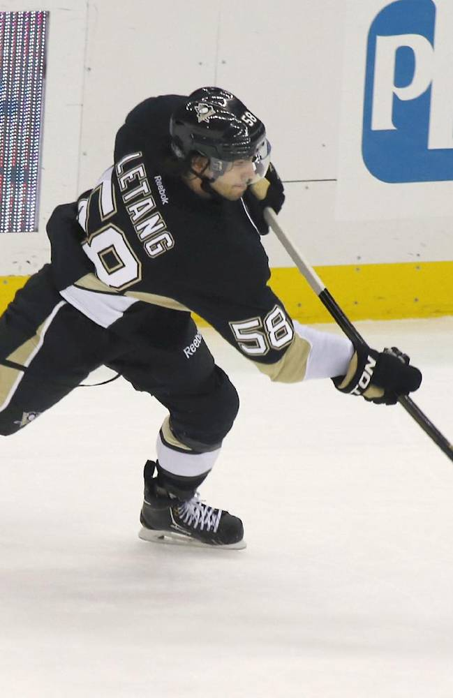 Pittsburgh Penguins' Kris Letang (58) shoots and score the game tying goal, in the third period of the NHL preseason hockey game against the Chicago Blackhawks on Monday, Sept. 23, 2013, in Pittsburgh. The Penguins won 3-2 in a shootout