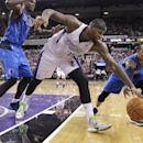 Sacramento Kings center DeMarcus Cousins, center, scrambles after the ball against Dallas Mavericks guard Monta Ellis, right, as Mavericks center Samuel Dalembert watches during the third quarter of an NBA basketball game, Sunday, April 6, 2014, in Sacra