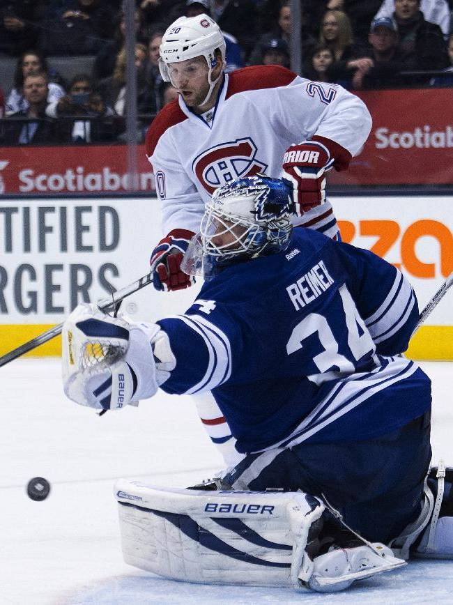 Toronto Maple Leafs' James Reimer, (34) makes a save as Montreal Canadiens forward Thomas Vanek looks on during third period of an NHL hockey game in Toronto on Saturday, March 22, 2014