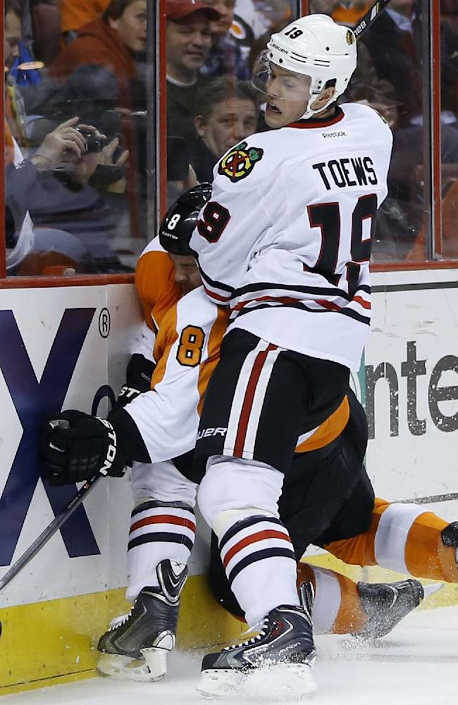 Chicago Blackhawks' Jonathan Toews (19) checks Philadelphia Flyers' Nicklas Grossmann (8), of Sweden, into the boards during the first period of an NHL hockey game, Tuesday, March 18, 2014, in Philadelphia