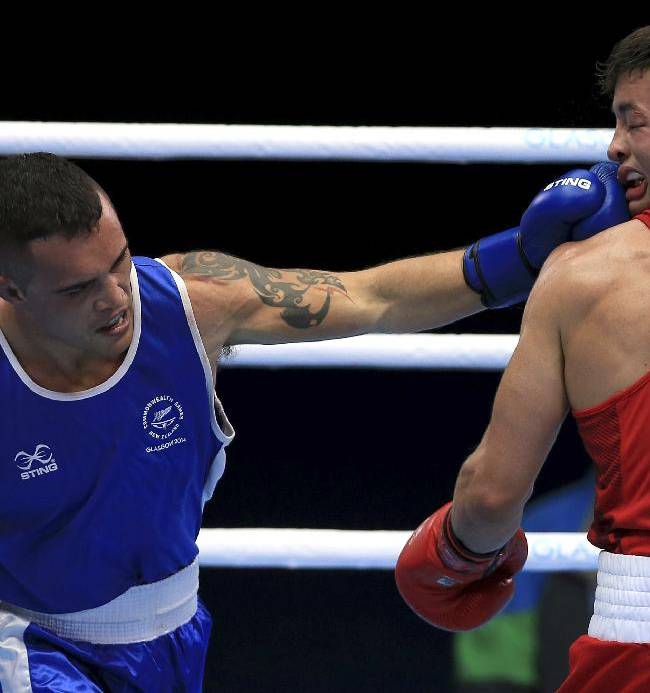 England's Scott Fitzgerald, right, takes a punch to the face against New Zealand's Bowyn Morgan  in the men's Welterweight quarterfinal  Commonwealth Games Glasgow 2014, in Glasgow Scotland Wednesday July 30, 2014
