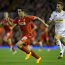 Liverpool's Philippe Coutinho, left, keeps the ball from Swansea's Angel Rangel during the English League Cup soccer match between Liverpool and Swansea at Anfield Stadium, Liverpool, England, Tuesday Oct. 28, 2014