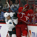 San Jose Sharks' Joe Pavelski (8) collides with Carolina Hurricanes' Brad Malone (24) during the second period of an NHL hockey game in Raleigh, N.C., Sunday, Nov. 16, 2014 The Associated Press