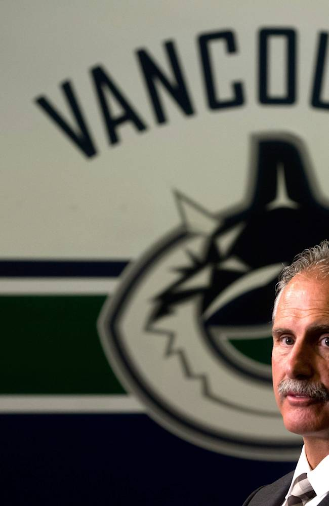 Vancouver Canucks' head coach Willie Desjardins stands for television interviews after he was hired by the NHL hockey team in Vancouver, B.C., on Monday, June 23, 2014. Desjardins replaces John Tortorella who was fired at the end of last season