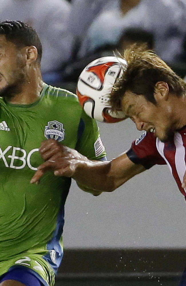 Chivas USA's Akira Kaji, right, heads the ball away from Seattle Sounders' Lamar Neagle during the first period of an MLS soccer match Wednesday, Sept. 3, 2014, in Carson, Calif
