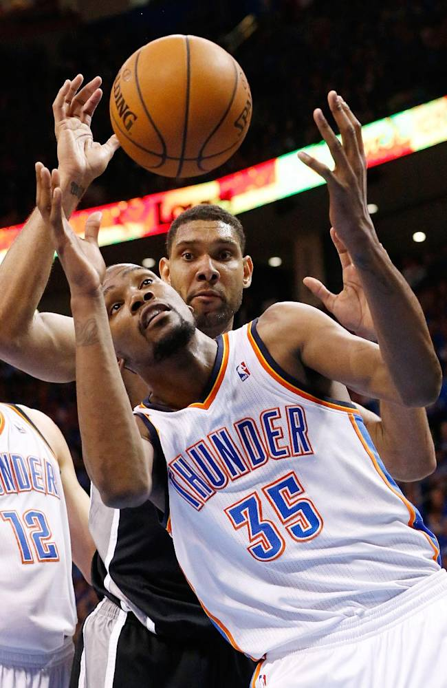Oklahoma City Thunder forward Kevin Durant (35) reaches for a rebound in front of San Antonio Spurs forward Tim Duncan in the fourth quarter of Game 3 of an NBA basketball playoff series in the Western Conference finals, Sunday, May 25, 2014, in Oklahoma City. Oklahoma City won 106-97