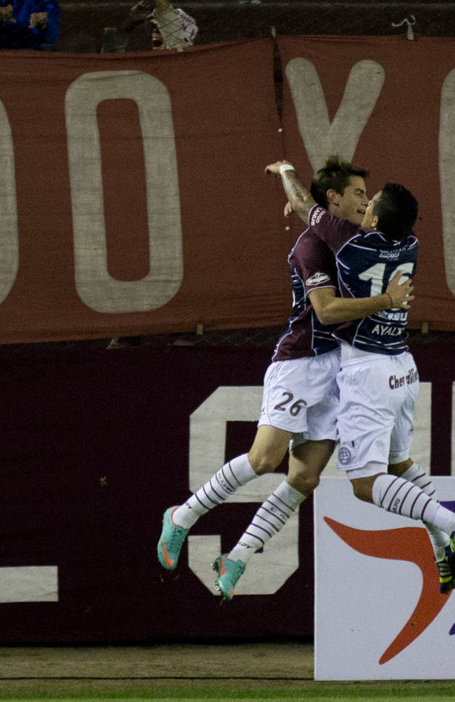 Lucas Melano of Argentina's Lanus, left, and Victor Ayala celebrates after Melano scored against Chile's Universidad de Chile during a Copa Sudamericana soccer match Wednesday, Sept. 18, 2013, in Buenos Aires, Argentina