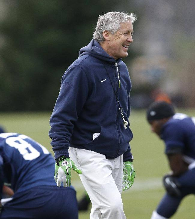 Seattle Seahawks coach Pete Carroll walks on the field as players stretch for NFL football practice Thursday, Jan. 2, 2014, in Renton, Wash