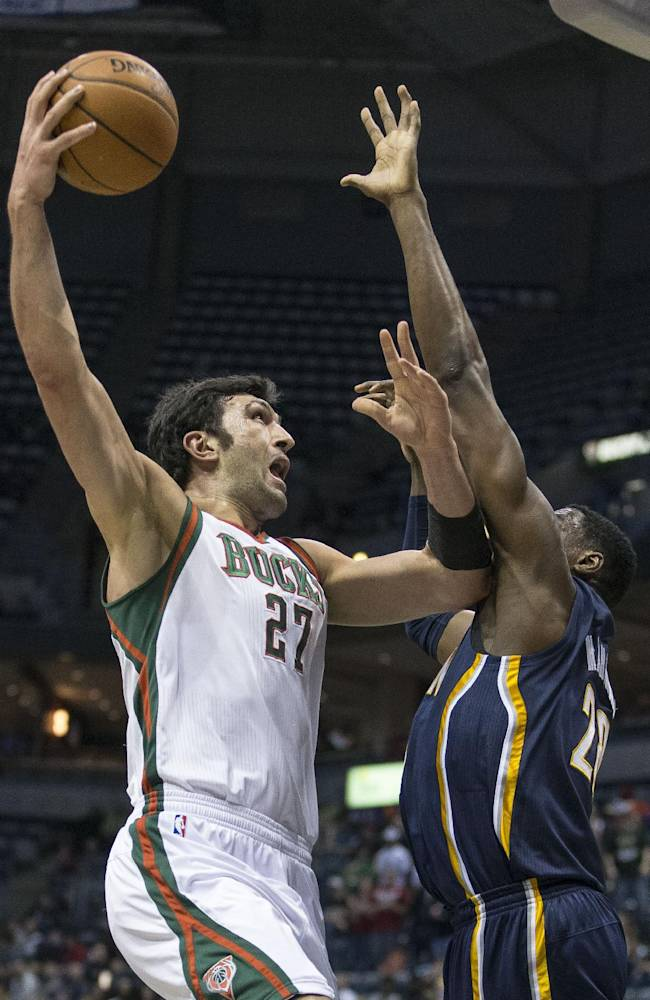 Milwaukee Bucks' Zaza Pachulia shoots the ball over Indiana Pacers' Ian Mahinmi during the first half of an NBA basketball game on Wednesday, April 9, 2014, in Milwaukee