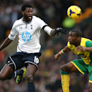 Norwich City's Sebastien Bassong, right, and Tottenham Hotspur's Emmanuel Adebayor compete for the ball during their English Premier League soccer match at Carrow Road, Norwich, England, Sunday, Feb. 23, 2014