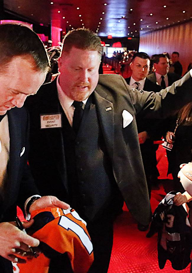 Denver Broncos quarterback Peyton Manning, left, signs autographs while walking the red carpet to the Ovation Theater, Friday March 14 2014, at the Maxwell Football Awards at the Revel Casino and Hotel in Atlantic City, N.J