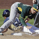 Milwaukee Brewers' Carlos Gomez slides safely under the tag of Oakland Athletics' Jake Elmore as he steals third base during the fifth inning of an exhibition baseball game Wednesday, March 5, 2014, in Phoenix The Associated Press