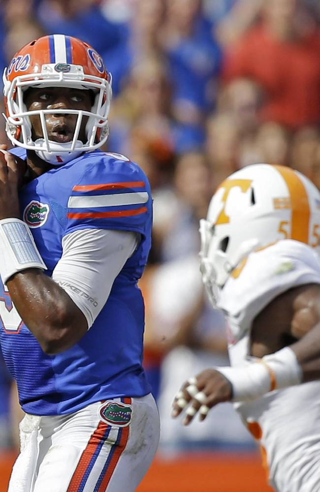 Florida quarterback Tyler Murphy, left, looks for a receiver as he is pressured by Tennessee defensive lineman Jacques Smith (55) during the first half of an NCAA college football game in Gainesville, Fla., Saturday, Sept. 21, 2013