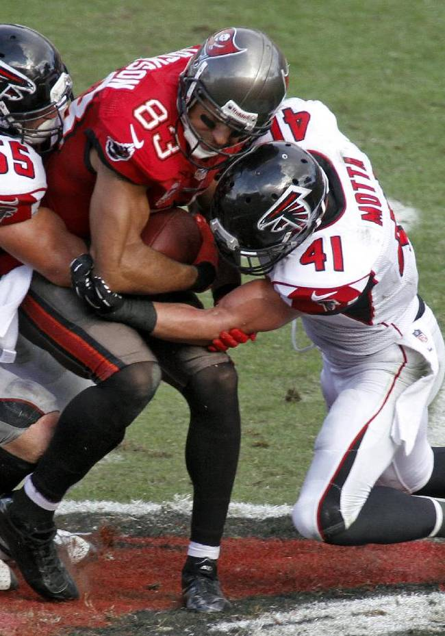 Tampa Bay Buccaneers wide receiver Vincent Jackson (83) is sandwiched by Atlanta Falcons outside linebacker Paul Worrilow (55) and strong safety Zeke Motta (41) after a reception during the fourth quarter of an NFL football game on Sunday, Nov. 17, 2013, in Tampa, Fla