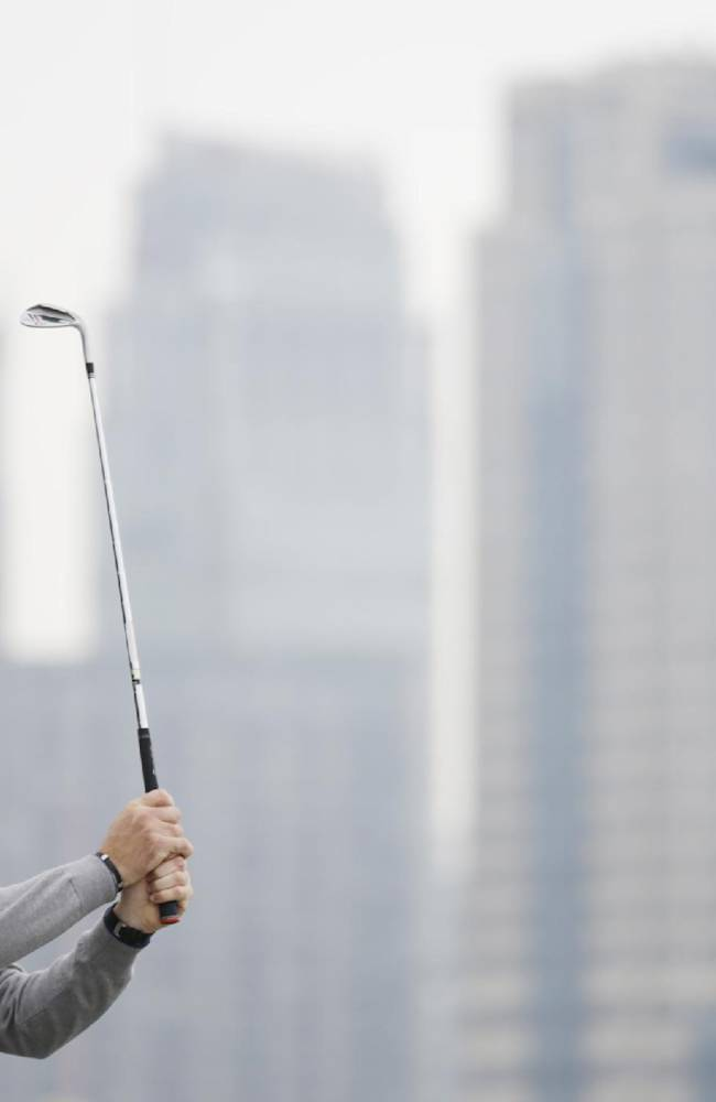 Peter Hanson of Sweden looks at his tee during a photo call ahead of the Masters golf tournament in Shanghai, China, Tuesday, Oct. 22, 2013. The Masters will begin on Oct. 24 at the Lake Malaren Golf Club