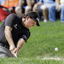 Phil Mickelson hits from the sand to the 15th green during the first round of the Bridgestone Invitational golf tournament Thursday, July 31, 2014, at Firestone Country Club in Akron, Ohio. (AP Photo/Mark Duncan)
