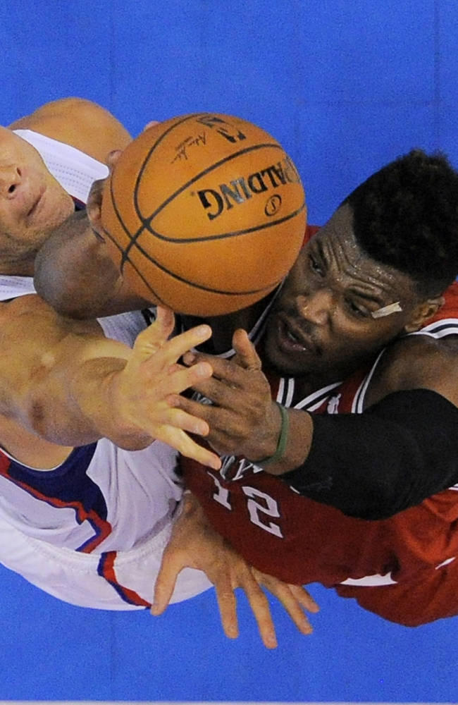 Milwaukee Bucks forward Jeff Adrien, right, goes up for a shot as Los Angeles Clippers forward Blake Griffin defends during the second half of an NBA basketball game, Monday, March 24, 2014, in Los Angeles. The Clippers won 106-98