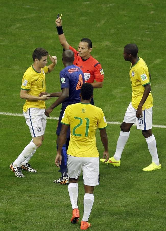 Referee Djamel Haimoudi from Algeria shows a yellow card to Brazil's Oscar, left, during the World Cup third-place soccer match between Brazil and the Netherlands at the Estadio Nacional in Brasilia, Brazil, Saturday, July 12, 2014