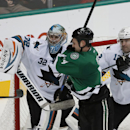 San Jose Sharks' Alex Stalock (32) uses his stick to deflect a shot under pressure from Dallas Stars left wing Jamie Benn (14) as Sharks' Patrick Marleau (12) assists during the third period of an NHL hockey game, Saturday, Nov. 8, 2014, in Dallas. The Sh