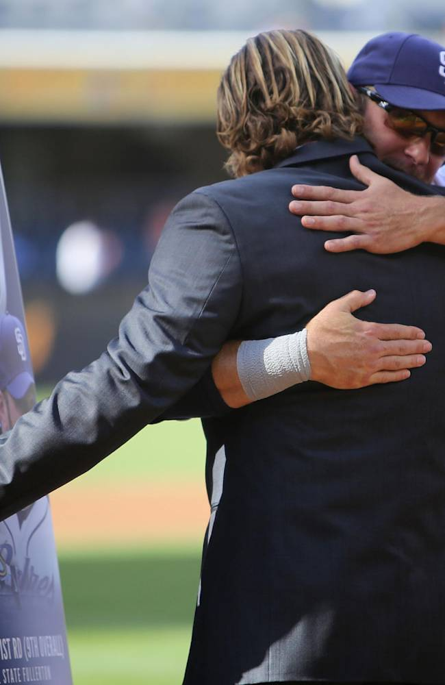 San Diego Padres' Hall of Fame pitcher Trevor Hoffman, left, hugs Padres' Mark Kotsay, right, after he presented a custom surfboard to Kotsay before a baseball game against the Arizona Diamondbacks on Thursday, Sept. 26, 2013, in San Diego