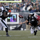 Philadelphia Eagles' Nick Foles (9) tosses to LeSean McCoy (25) as he is tackled by Arizona Cardinals' Dan Williams (92) and Frostee Rucker (98) during the first half of an NFL football game on Sunday, Dec. 1, 2013, in Philadelphia The Associated Press