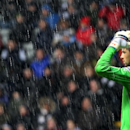 Newcastle United's goalkeeper Tim Krul covers his head with his hands to shelter from the heavy rain during their English Premier League soccer match against Tottenham Hotspurs at St James' Park, Newcastle, England, Wednesday, Feb. 12, 2014