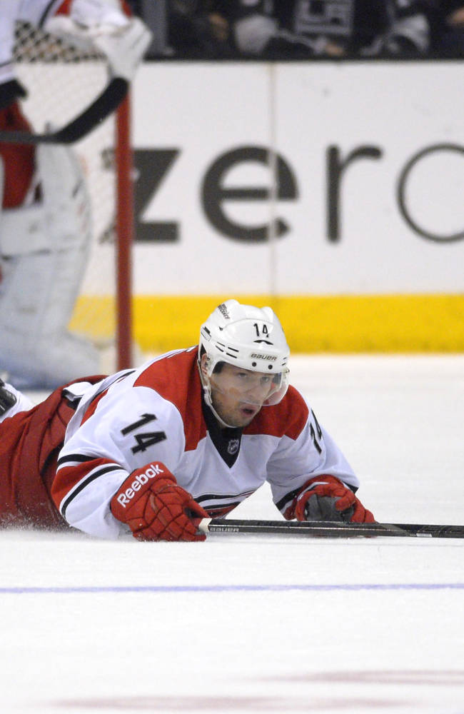 Carolina Hurricanes left wing Nathan Gerbe dives for the puck during the first period of an NHL hockey game against the Los Angeles Kings, Saturday, March 1, 2014, in Los Angeles