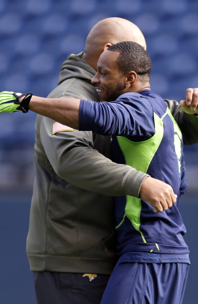 Seattle Seahawks' Percy Harvin, right, hugs an unidentified member of the Minnesota Vikings before an NFL football game on Sunday, Nov. 17, 2013, in Seattle