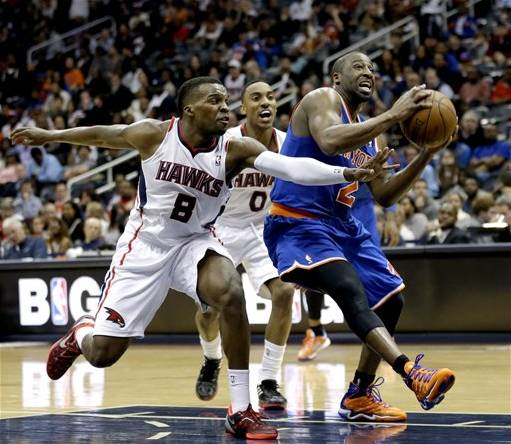 New York Knicks' Raymond Felton, right, drives to the hoop past Atlanta Hawks' Shelvin Mack in the fourth quarter of an NBA basketball game, Wednesday, April 3, 2013, in Atlanta. New York won 95-82