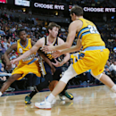 Utah Jazz forward Gordon Hayward, center, loses control of the ball as Denver Nuggets guard Aaron Brooks, left, and center Timofey Mozgov, of Russia, cover in the first quarter of an NBA basketball game in Denver on Saturday, April 12, 2014 The Associated