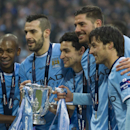 Manchester City's players from the left, Fernandinho Luiz Roza, Alvaro Negredo, Jesus Navas, Javi Garcia and David Silva hold the trophy after their team's 3-1 win against Sunderland in the League Cup Final at Wembley Stadium, London, England, Sunday Marc