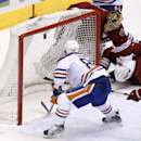Edmonton Oilers' Sam Gagner (89) scores a goal as Phoenix Coyotes' Thomas Greiss, of Germany, top right, is caught behind the net during the third period of an NHL hockey game, Friday, April 4, 2014, in Glendale, Ariz. The Oilers defeated the Coyotes in