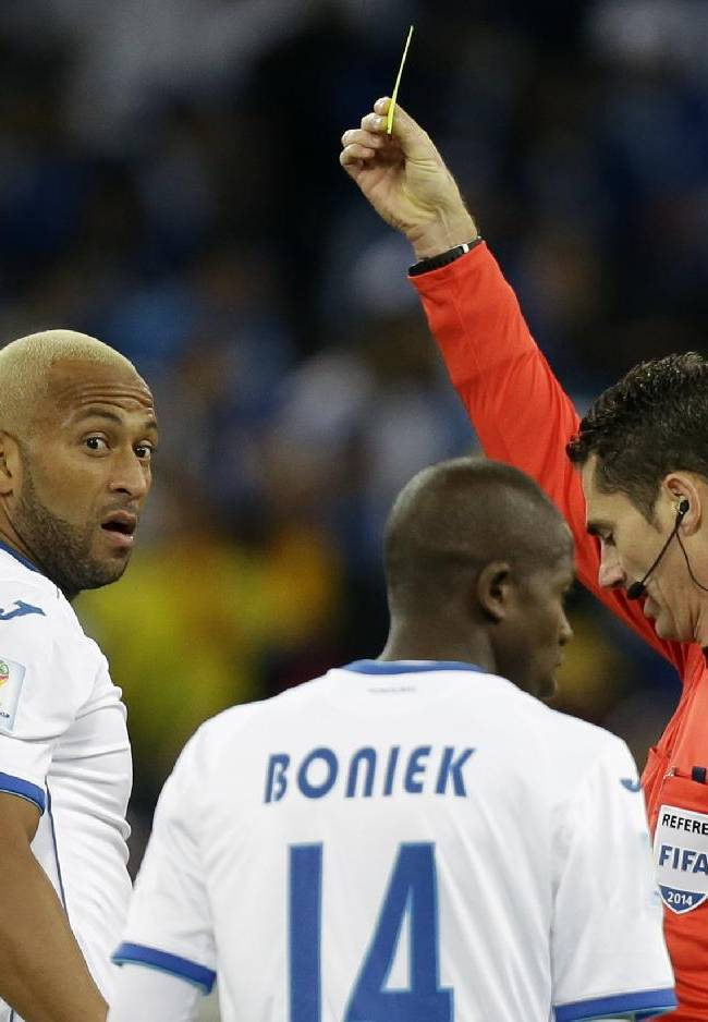 Referee Benjamin Williams, right, from Australia books Honduras' Victor Bernardez, left, during the group E World Cup soccer match between Honduras and Ecuador at the Arena da Baixada in Curitiba, Brazil, Friday, June 20, 2014