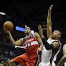 Washington Wizards' Garrett Temple, left, shoots past Milwaukee Bucks' Caron Butler during the first half of an NBA basketball game Wednesday, Nov. 27, 2013, in Milwaukee The Associated Press