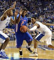 Boise State's Derrick Marks, center, attempts to fight through the defense of Kentucky's Aaron Harrison, left, and James Young during the first half of an NCAA college basketball game Tuesday, Dec. 10, 2013, in Lexington, Ky. (AP Photo/Timothy D. Easley)