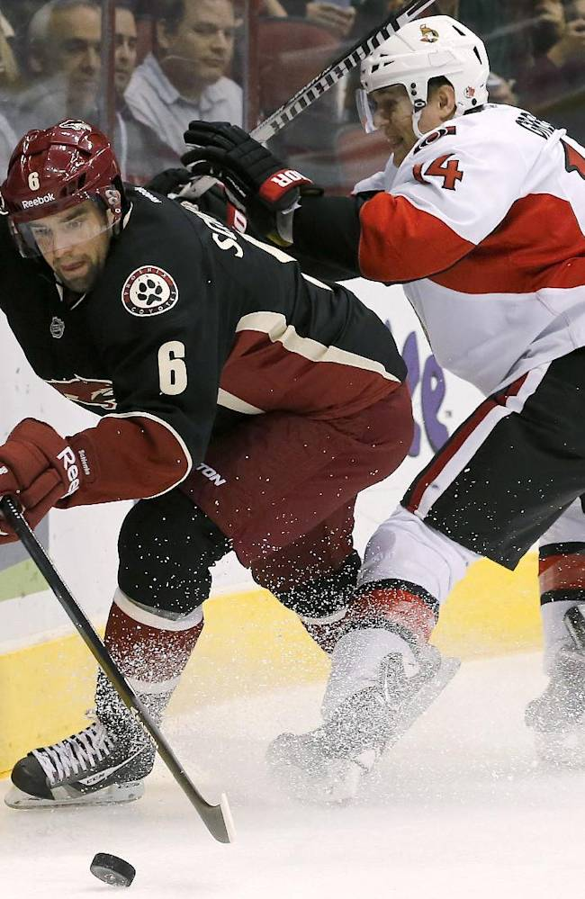Phoenix Coyotes' David Schlemko (6) tries to keep the puck away from Ottawa Senators' Colin Greening (14) during the first period in an NHL hockey game Tuesday, Oct. 15, 2013, in Glendale, Ariz