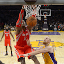 Houston Rockets center Dwight Howard, left, dunks as Los Angeles Lakers center Chris Kaman defends during the first half of an NBA basketball game, Wednesday, Feb. 19, 2014, in Los Angeles The Associated Press