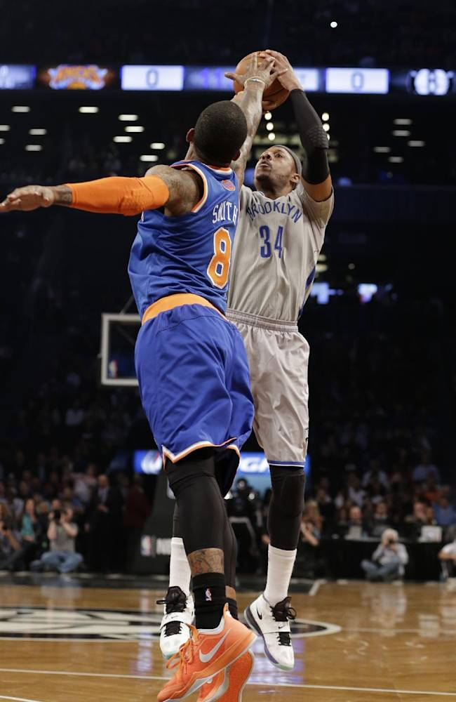 Brooklyn Nets' Paul Pierce (34) shoots over New York Knicks' J.R. Smith (8) during the first half of an NBA basketball game Tuesday, April 15, 2014, in New York